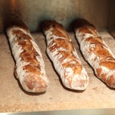 Baguettes ready to be taken out of the stone oven